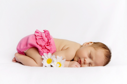Sleeping newborn baby girl with daisies